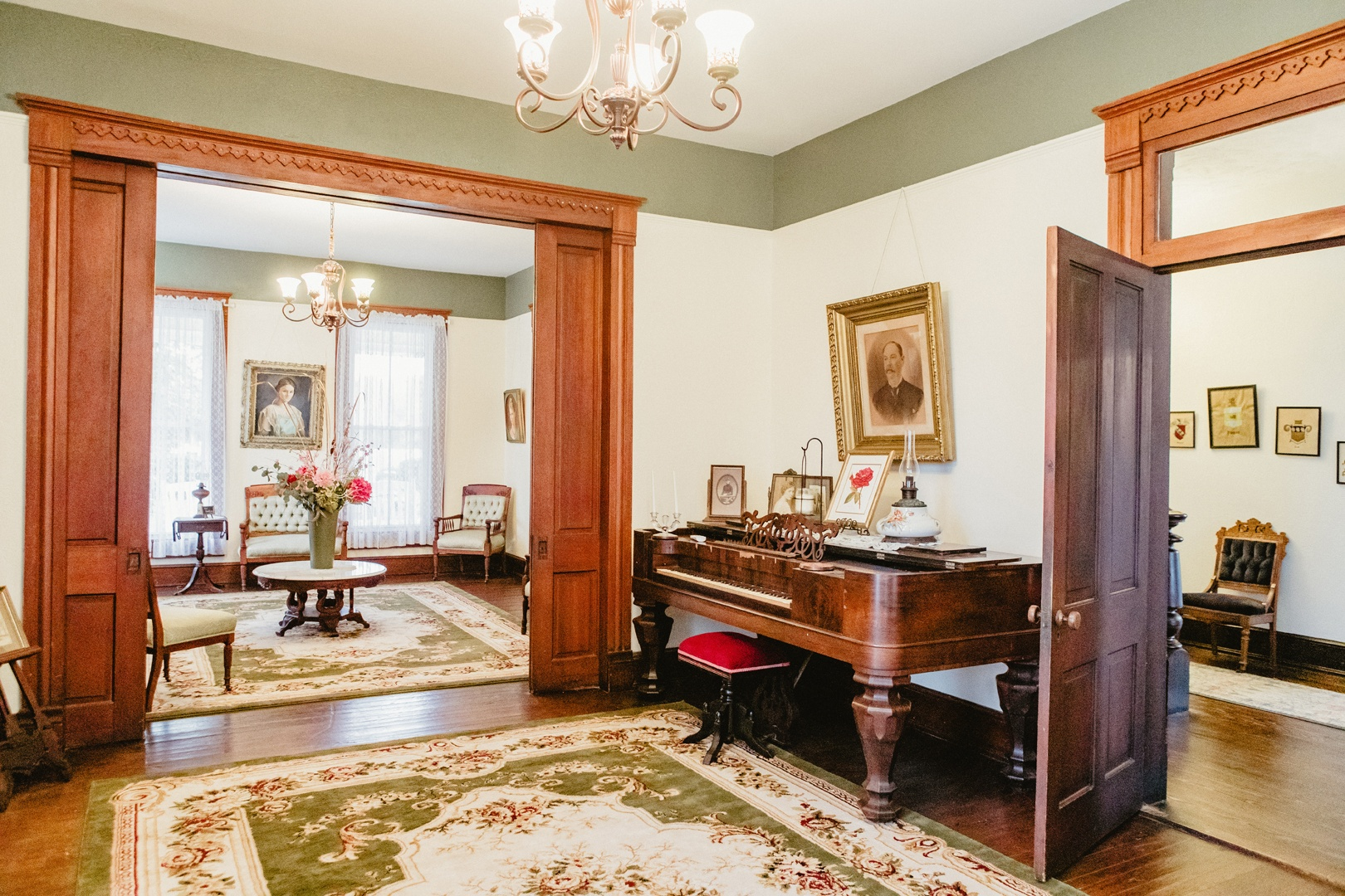 The double parlor is divided by large wooden doors.