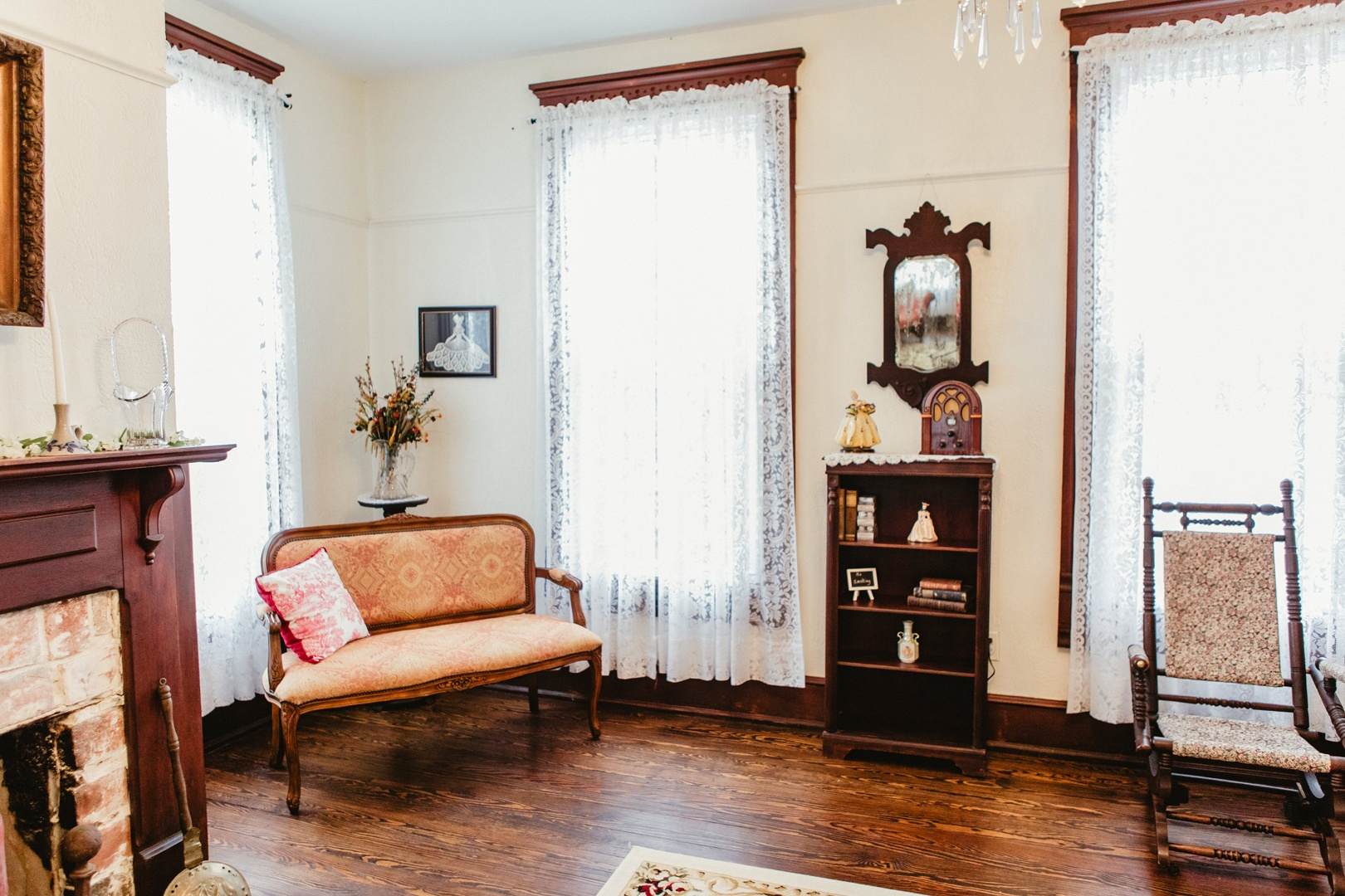 A Victorian style chair sits in the corner surround by tall windows draped in delicate white lace.