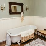 An old-fashioned cast-iron claw foot tub is draped with decorative blankets.