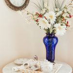 A stunning blue vase holds freshly picked farmland flowers and shares a table with a fine china tea set.