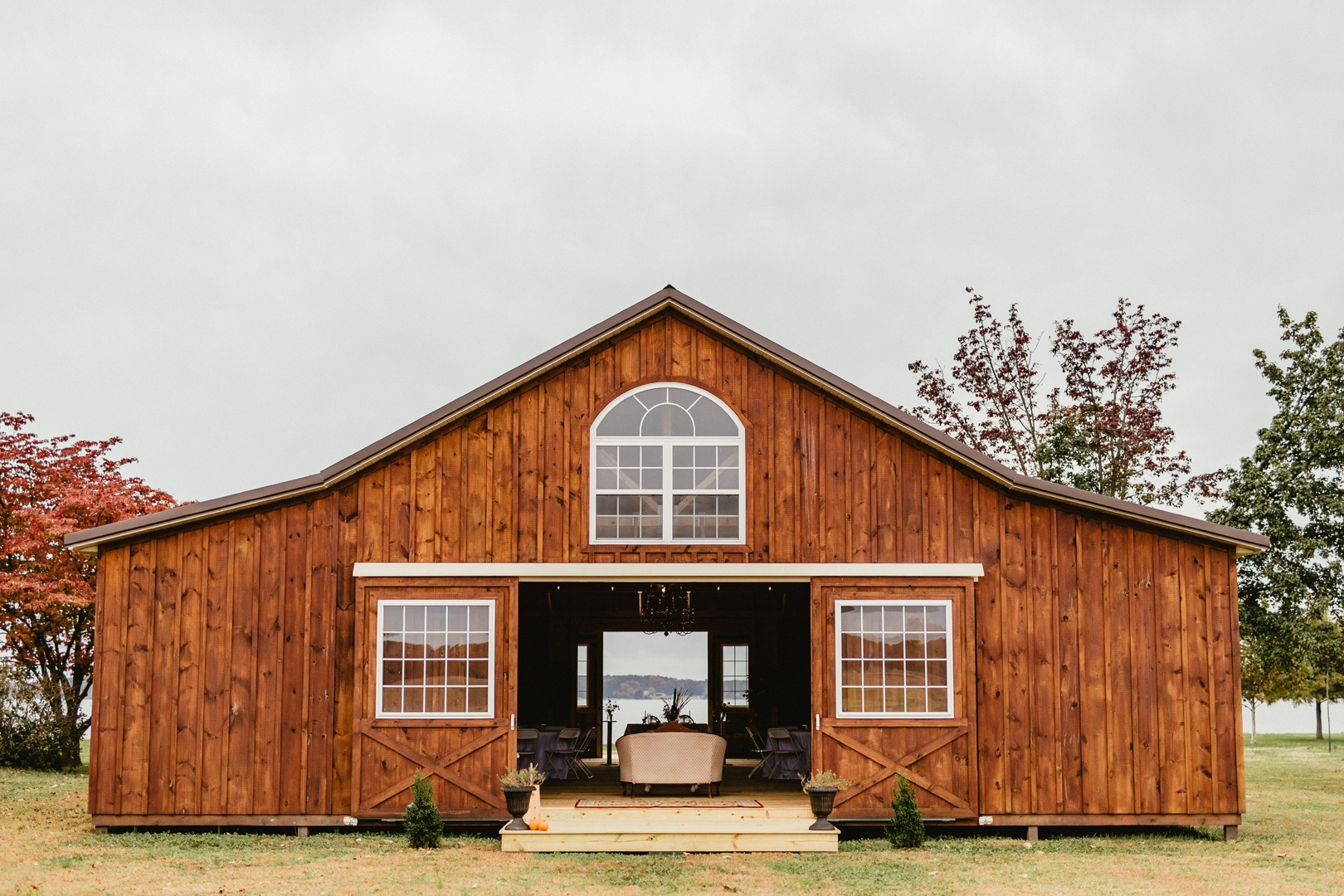 The exterior of the reception barn is a rusty, vibrant shade of red and has three large windows facing the farmlands and the Wicomico River.
