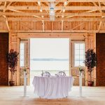 The interior of the reception barn facing the Wicomico River and decorated with pristine white drapery and Edison ceiling lighting.