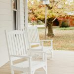 Two white rocking chairs sit on the riverside porch.