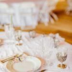 Delicate china, glassware, and silverware sit upon pristine white tablecloth inside the reception barn.