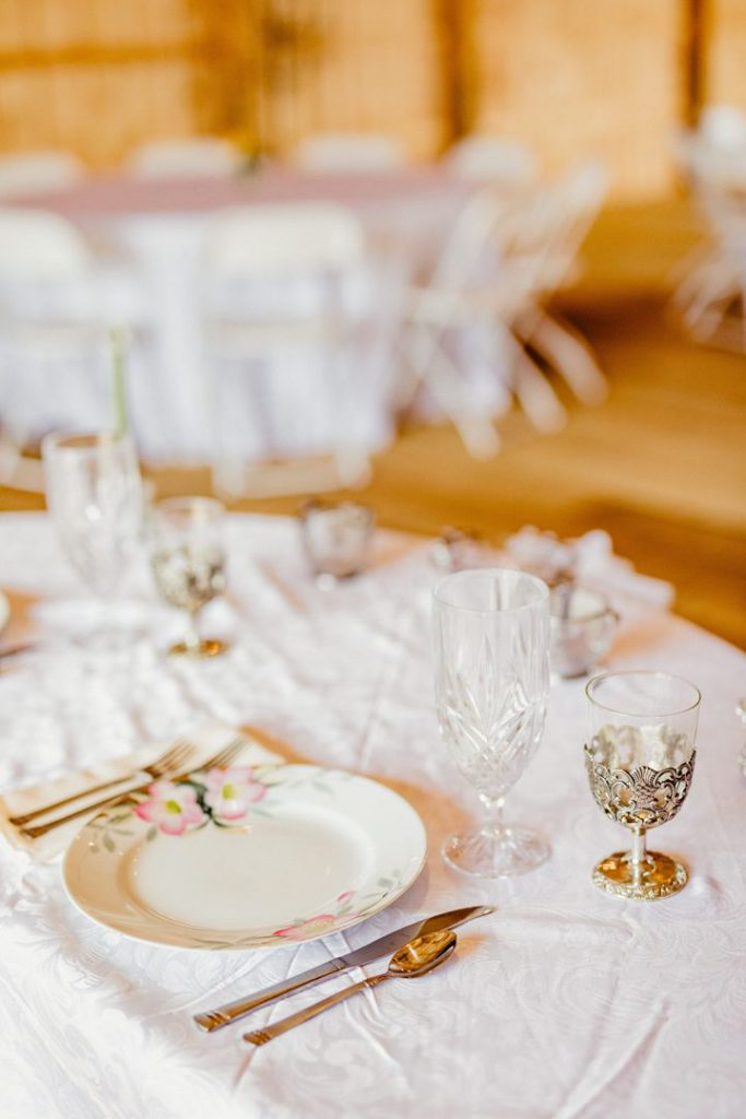 Delicate china, glassware, and silverware sit upon pristine white tablecloth inside the reception barn.