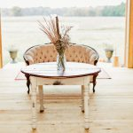A rustic wooden table and Victorian chair inside the reception barn