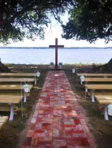 A red brick path leads from the manor in a straight line to the Wicomico shoreline. On either side are light wooden pews and at the end of the brick path is a wooden crucifix.